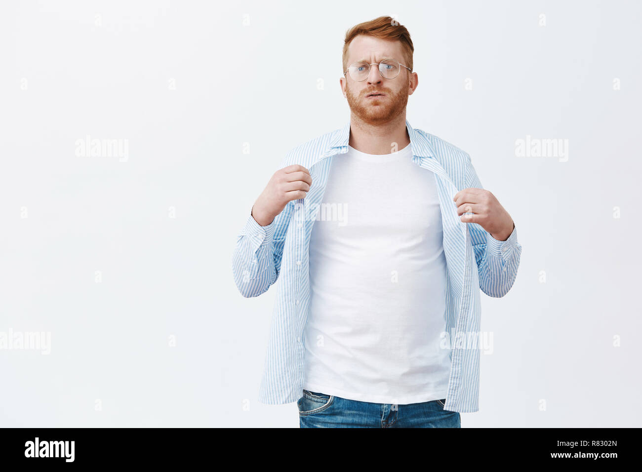 Very hot inside office, where is air cooler. Portrait of displeased suffering from summer warm weather male with red hair and beard in glasses, waving shirt to cool body, breathing out from heat - Stock Image