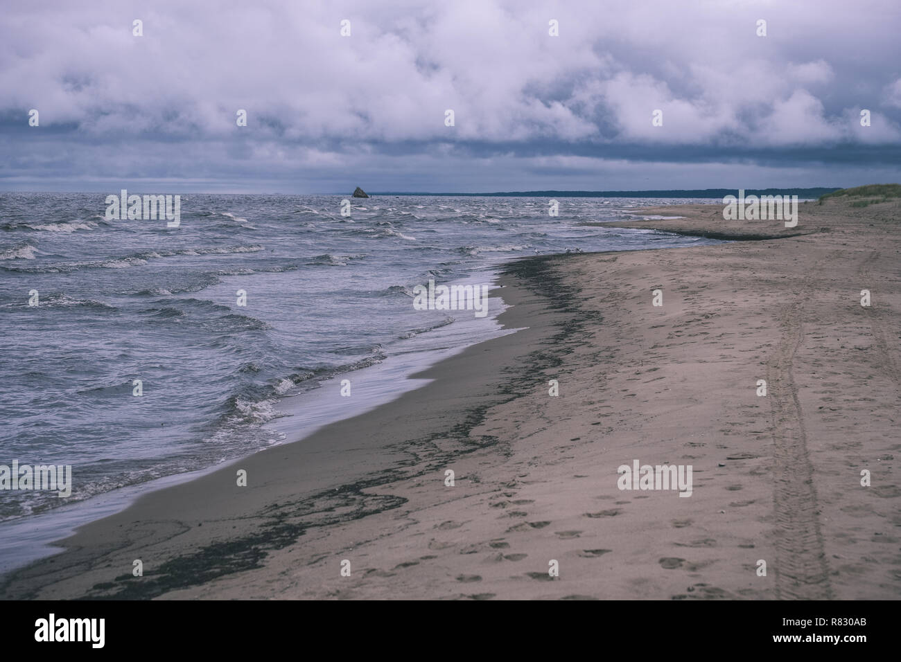 dirty beach by the sea with storm clouds above in calm evening - vintage old film look - Stock Image