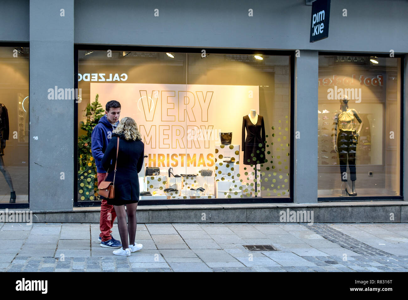 A young couple in Rennes, France stands in front of a storefront display stating 'Very Merry Christmas' in December. - Stock Image