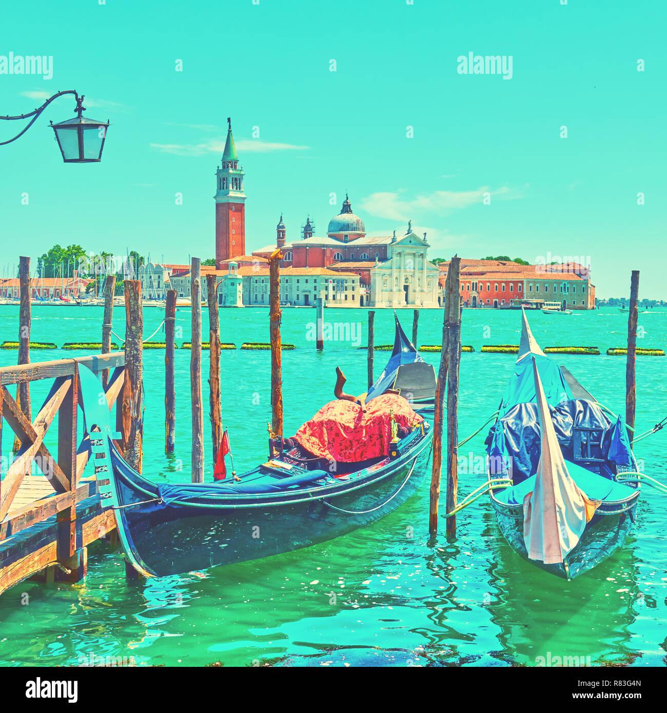 Moored gondolas and San Giorgio di Maggiore church in Venice, Italy - Stock Image