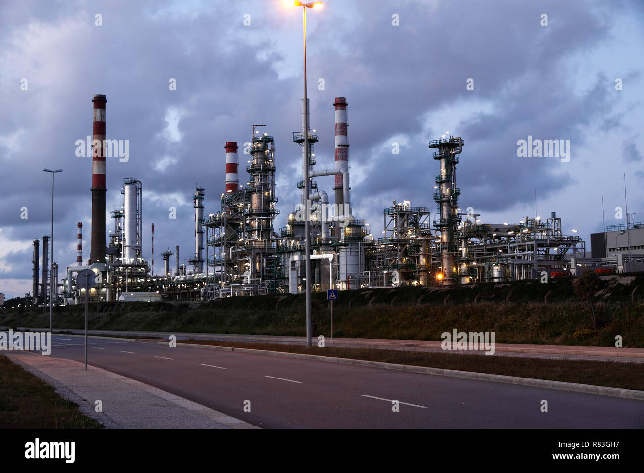 Oil refinery and powerplant near a road at dusk - Stock Image