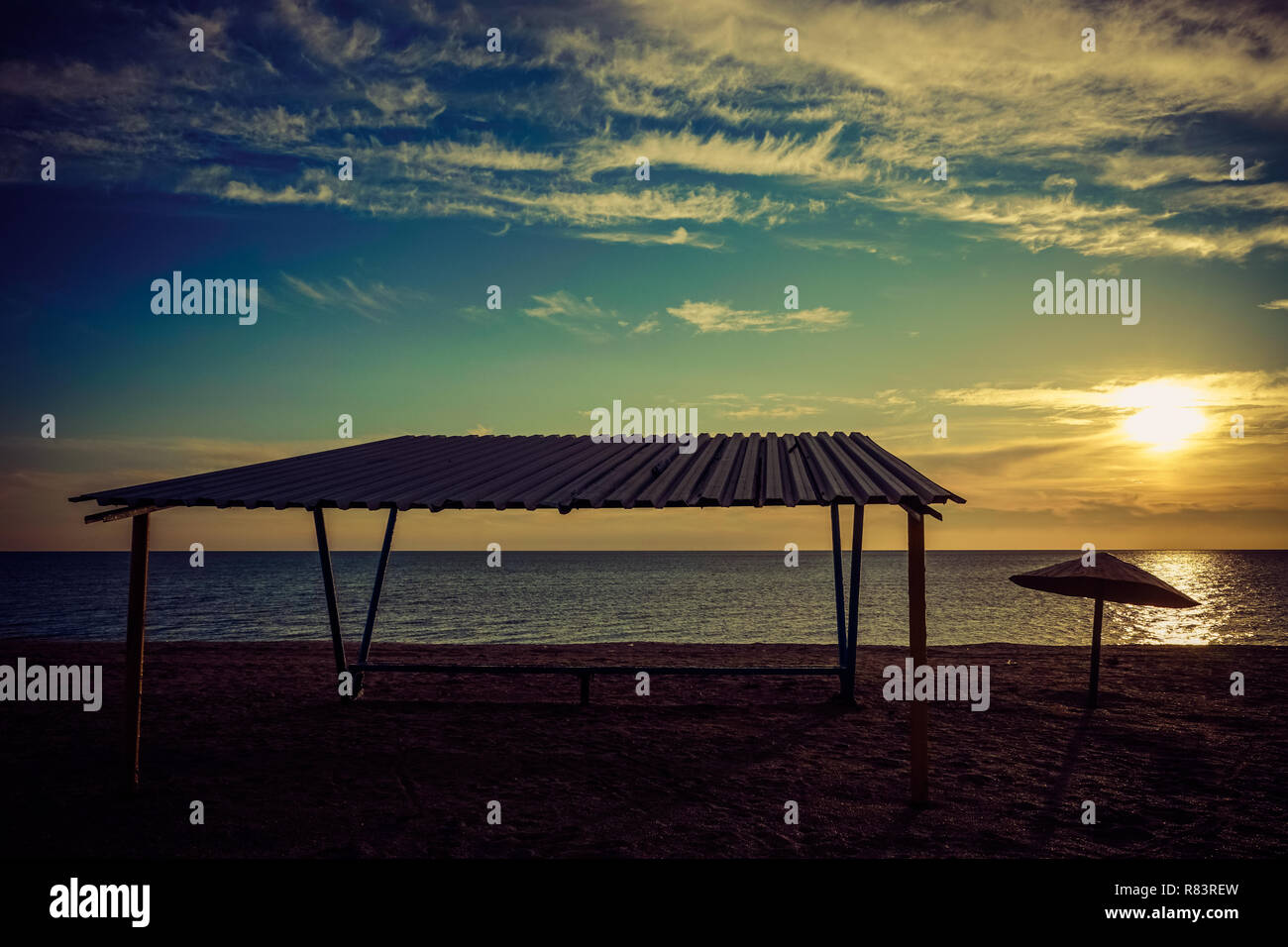 Canopy and old metal umbrella on sandy beach. Sunset sky with sun - Stock Image