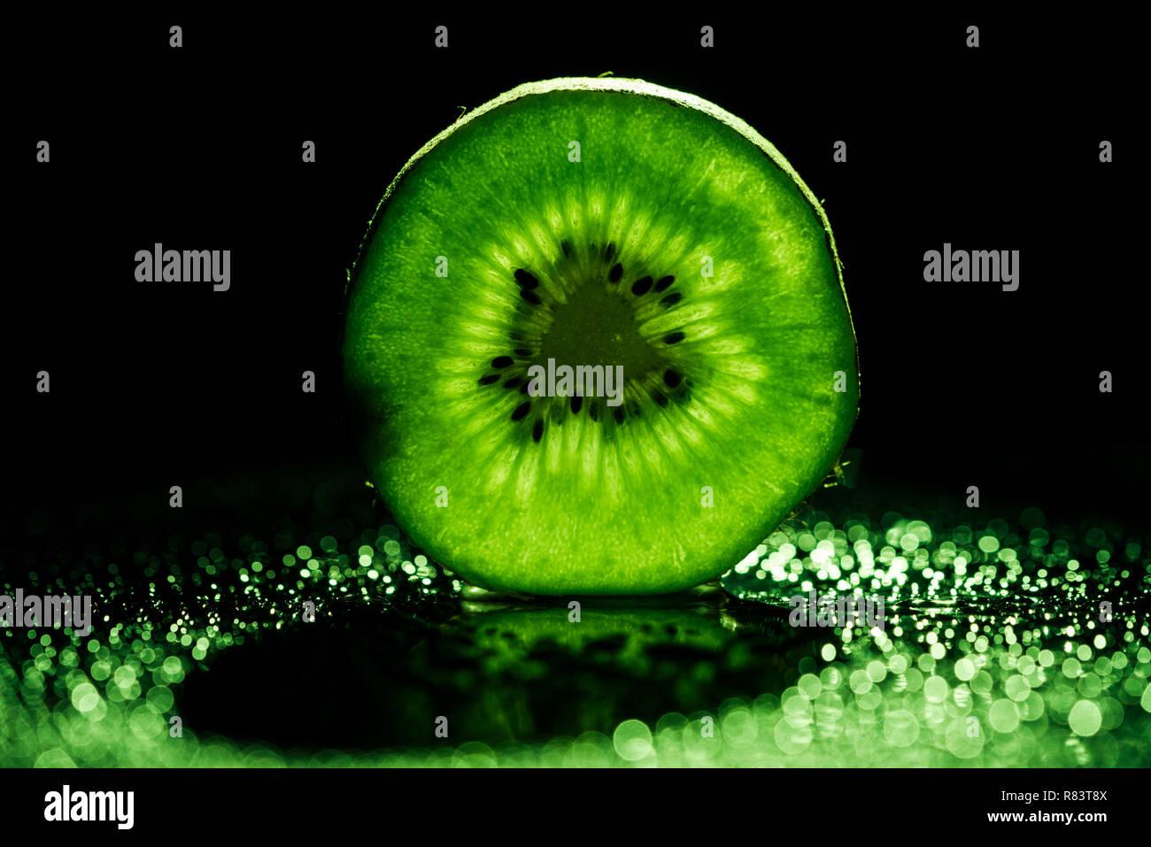 slice of kiwi fruit on black background with neon green backlit - Stock Image