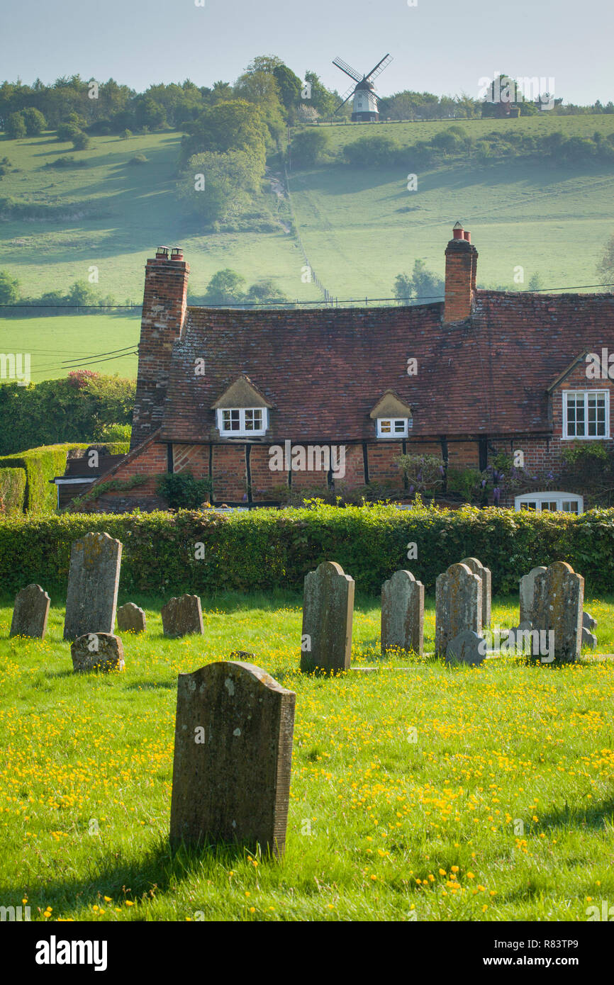 Brick and timber cottages at Turville, Buckinghamshire with Cobstone Windmill, famous for the film Chitty Chitty Bang Bang, on the hill above - Stock Image