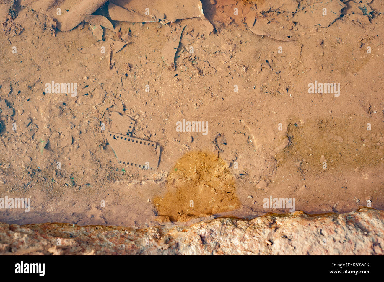 Mali, Africa. Dirty water puddles in a rural village near Bamako containing an old ruined film slide for photography - Stock Image