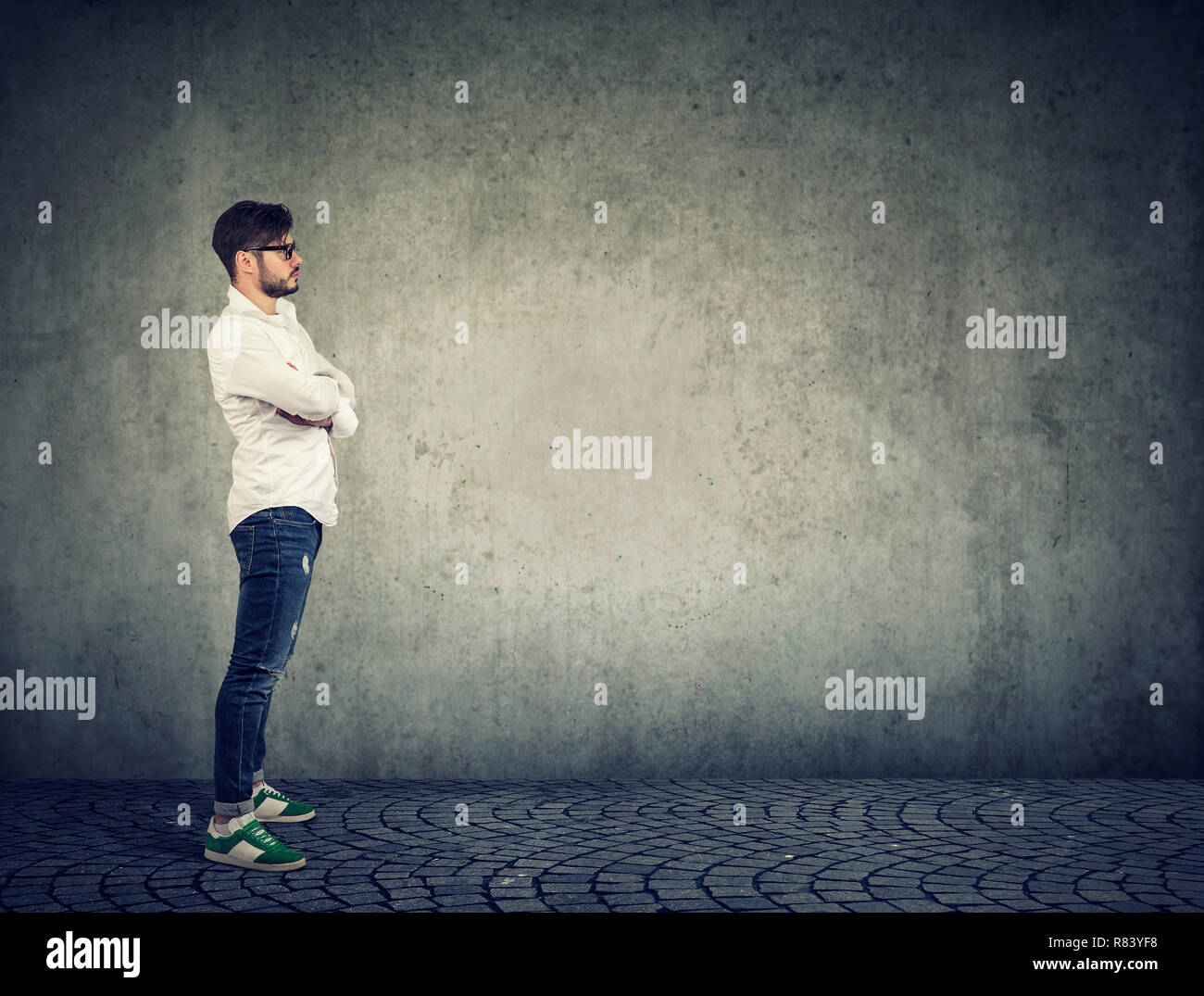 Side view of casual modern man in white shirt and denim standing against gray wall background - Stock Image