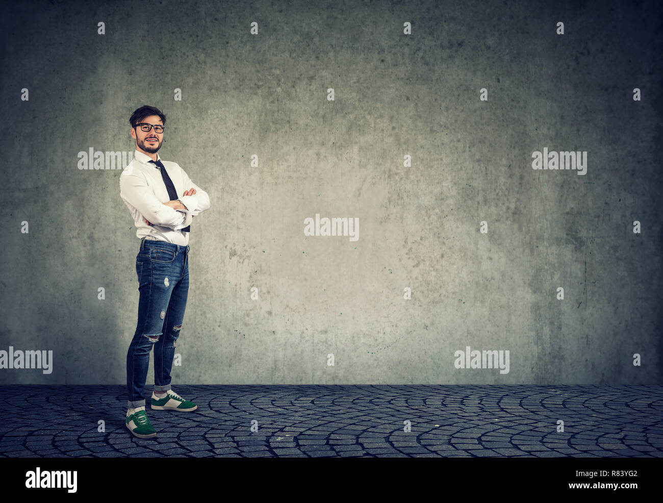 Happy casual modern man in white shirt and denim standing against gray wall background - Stock Image
