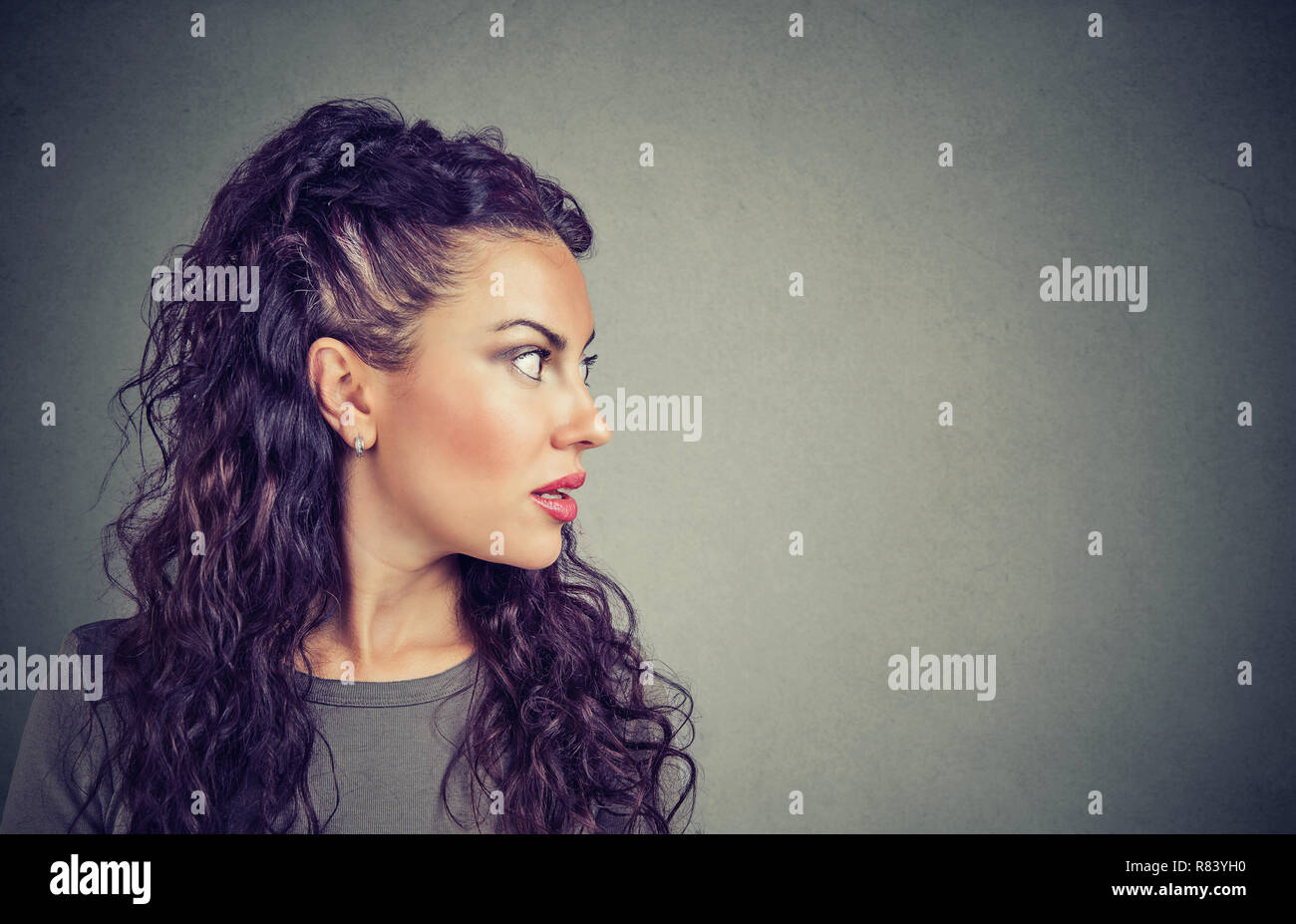 Closeup side view profile portrait woman talking with open mouth isolated on gray wall background. Face expression. Communication concept - Stock Image