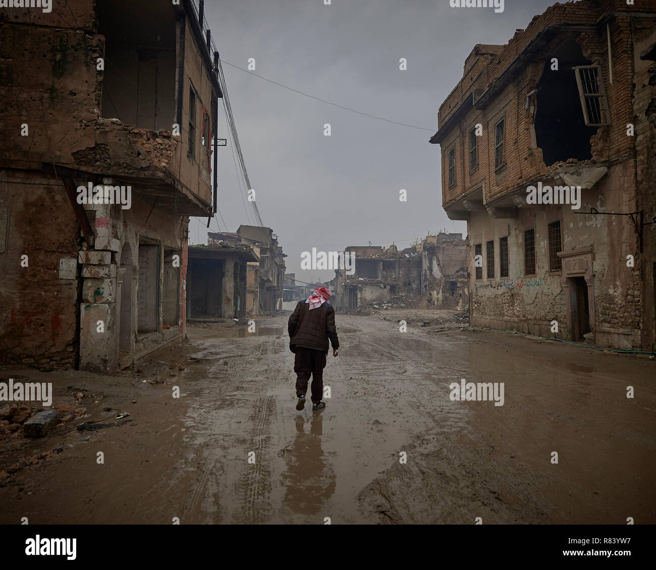 Qasim Yahia Ali, 75, walks along a rainy street in the old city of Mosul, Iraq. His house was destroyed during the 2017 Battle of Mosul. - Stock Image