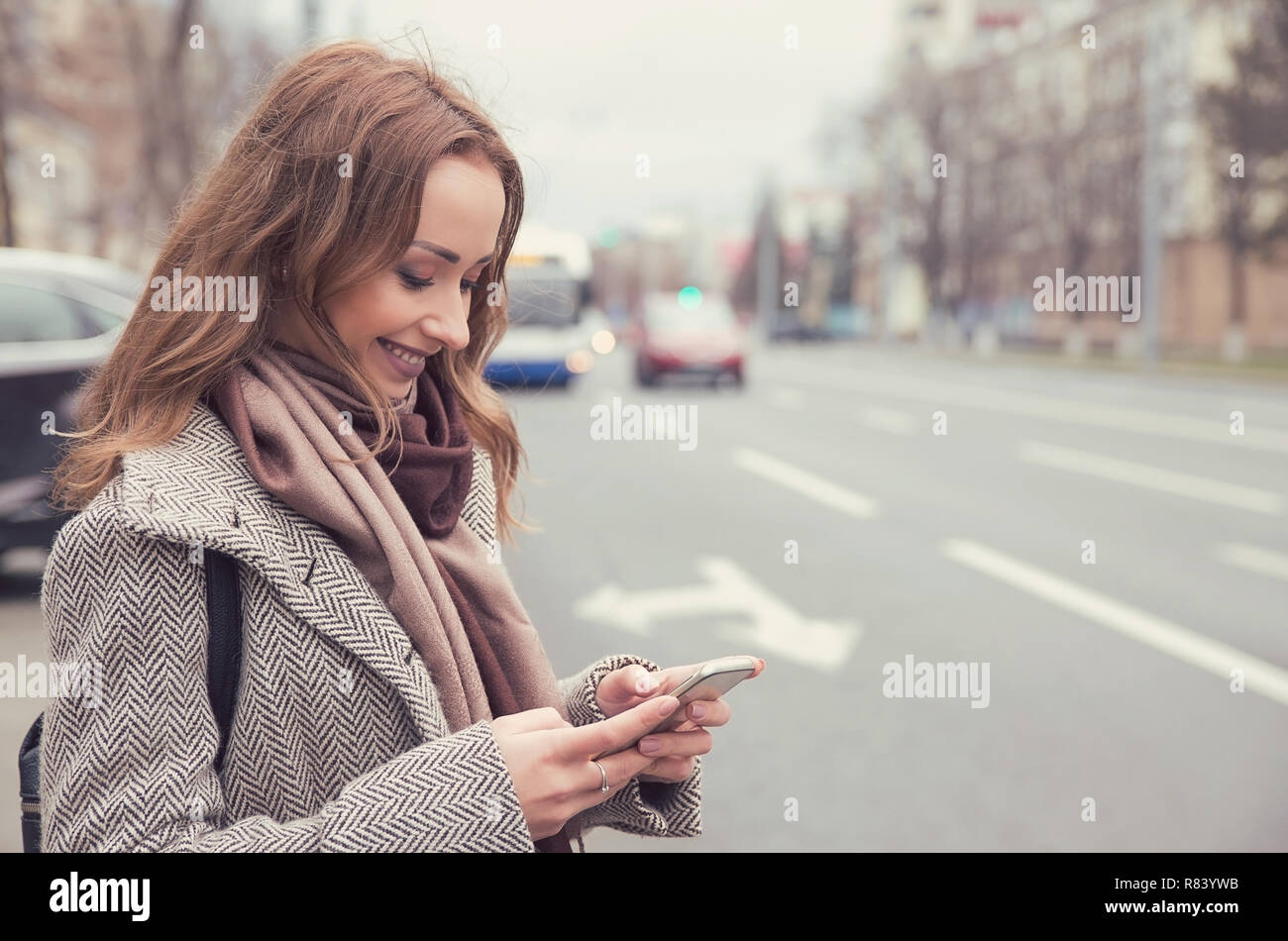 Smiling casual woman checking email via mobile phone waiting