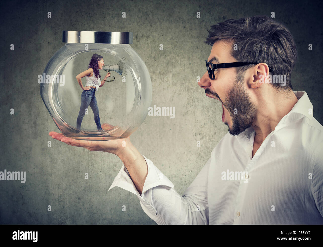 Frustrated businessman holding a glass jar with an angry screaming woman trapped in it Stock Photo