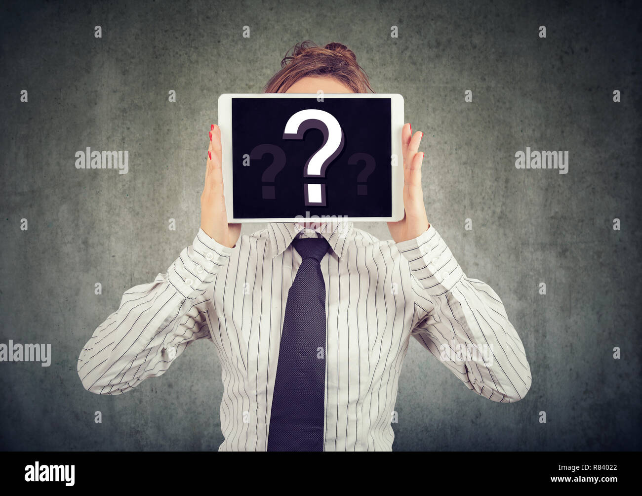Anonymous woman covering face with tablet showing question mark hiding personality in Internet - Stock Image