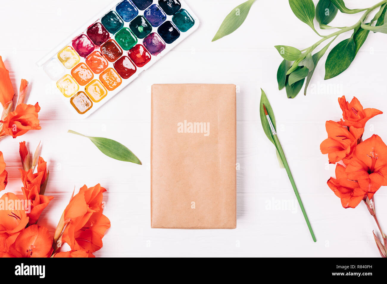 Blank gift box wrapped in crafting paper next to watercolor paints and brush among floral flat layout of red flowers and green leaves, top view on a w - Stock Image