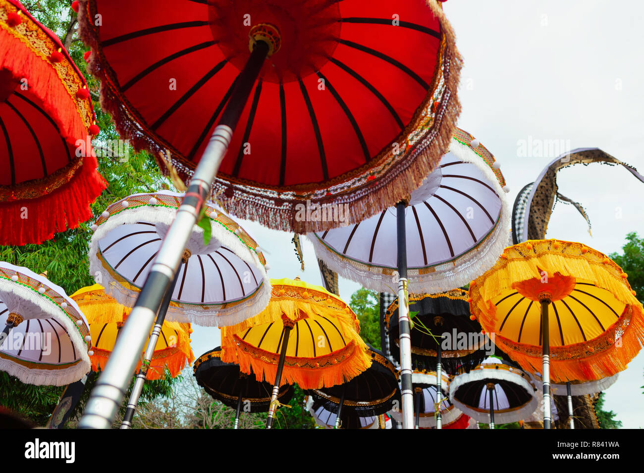 Group of beautiful Balinese flags and umbrellas at celebration ceremony in Hindu temple. Traditional design, arts festivals, culture of Bali island - Stock Image
