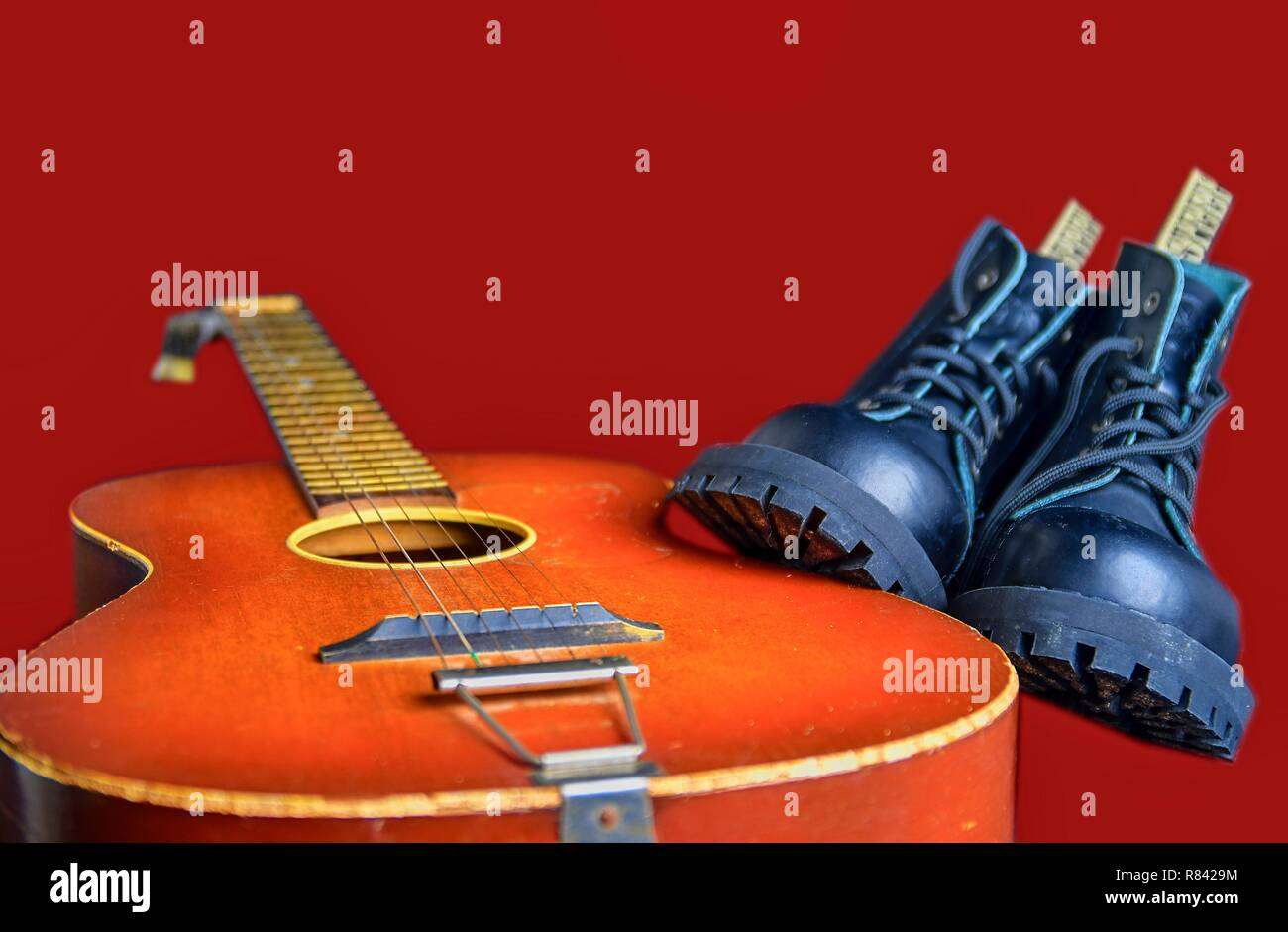 Rock and roll concept. Black boots and acoustic guitar. Rock and roll boots on claret background - Stock Image