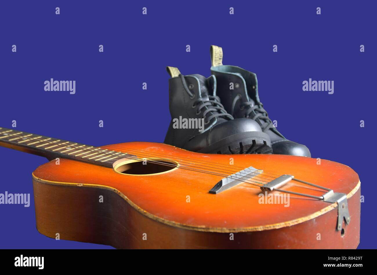 Rock and roll concept. Black boots and acoustic guitar. Rock and roll boots on navy blue background - Stock Image