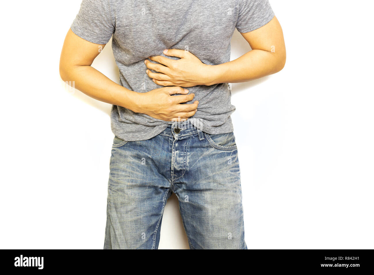 Man with stomach pain hand holding his aching belly isolated. - Stock Image