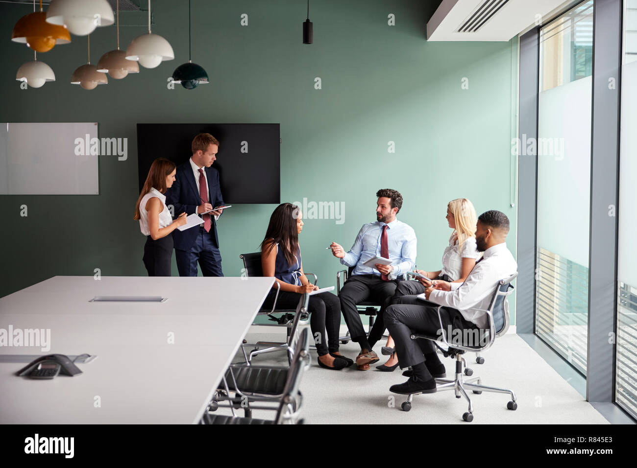Group Having Discussion At Graduate Recruitment Assessment Day Whilst Being Observed By Recruitment Team - Stock Image