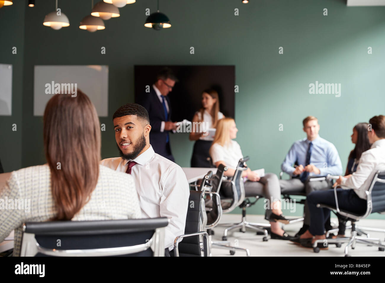 Businesswoman And Businessman Collaborating On Task Together At Graduate Recruitment Assessment Day - Stock Image