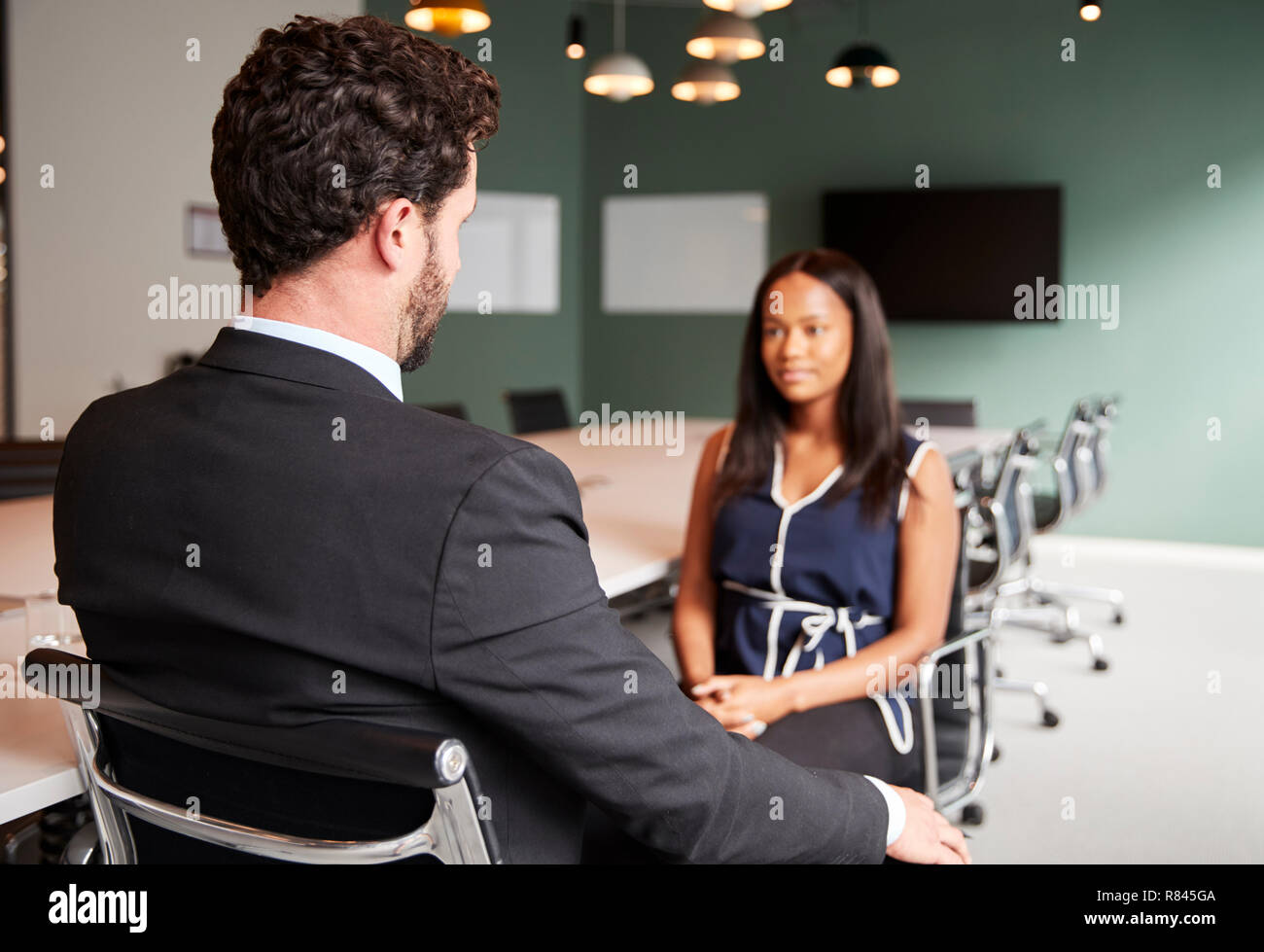 Businessman Interviewing Female Candidate At Graduate Recruitment Assessment Day In Office - Stock Image