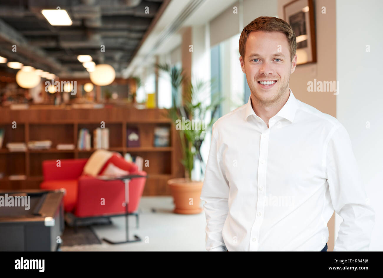 Portrait Of Young Businessman Standing In Modern Office At Graduate Recruitment Assessment Day - Stock Image