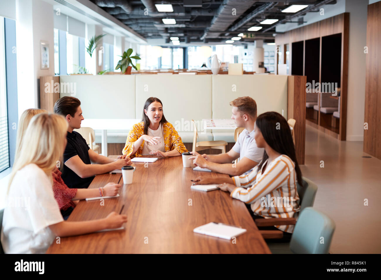 Group Of Young Candidates Sitting Around Table And Collaborating On Task At Business Graduate Recruitment Assessment Day - Stock Image