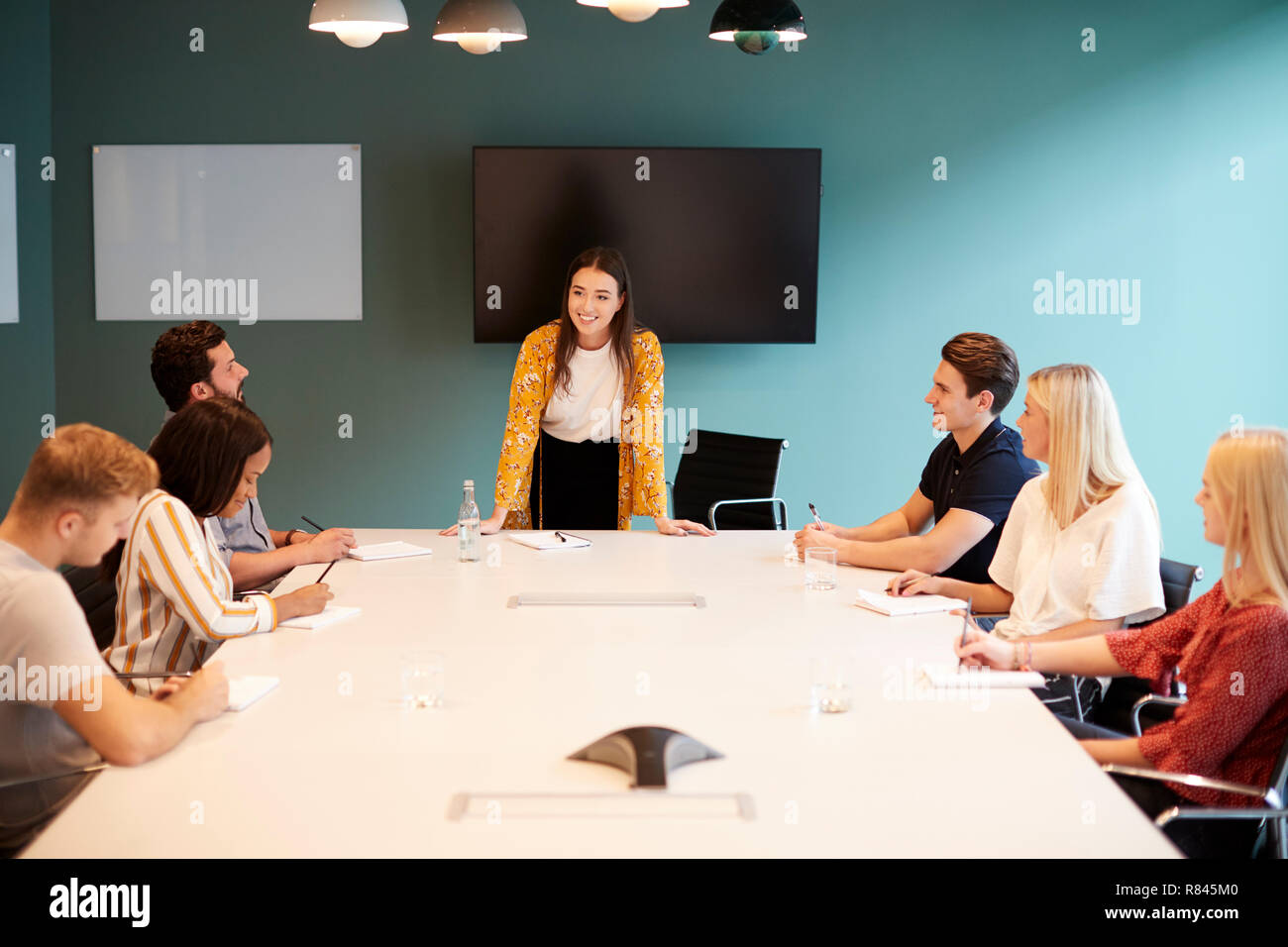 Businesswoman Addressing Group Of Candidates Meeting Around Table At Graduate Recruitment Assessment Day - Stock Image