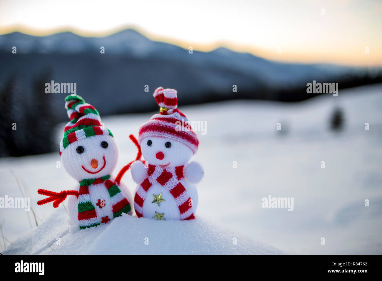 d5fb8e7662aaf Two small funny toys baby snowman in knitted hats and scarves in deep snow  outdoors on