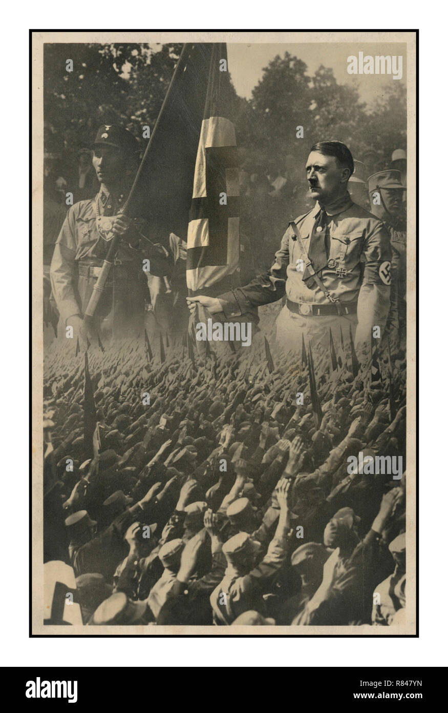 """Vintage 1930's Nazi propaganda postcard showing a crowd of saluting Germans superimposed on an enlarged image of Adolf Hitler with a member of the SA (Storm Trooper) who holds a swastika flag. Munich, Germany, c.1933 Taken by Hoffmann, Hitlers personal photographer... SA, abbreviation of Sturmabteilung (German: """"Assault Division""""), byname Storm Troopers or Brownshirts, German Sturmtruppen or Braunhemden, in the German Nazi Party, a paramilitary organization whose methods of violent intimidation played a key role in Adolf Hitler's rise to power. - Stock Image"""