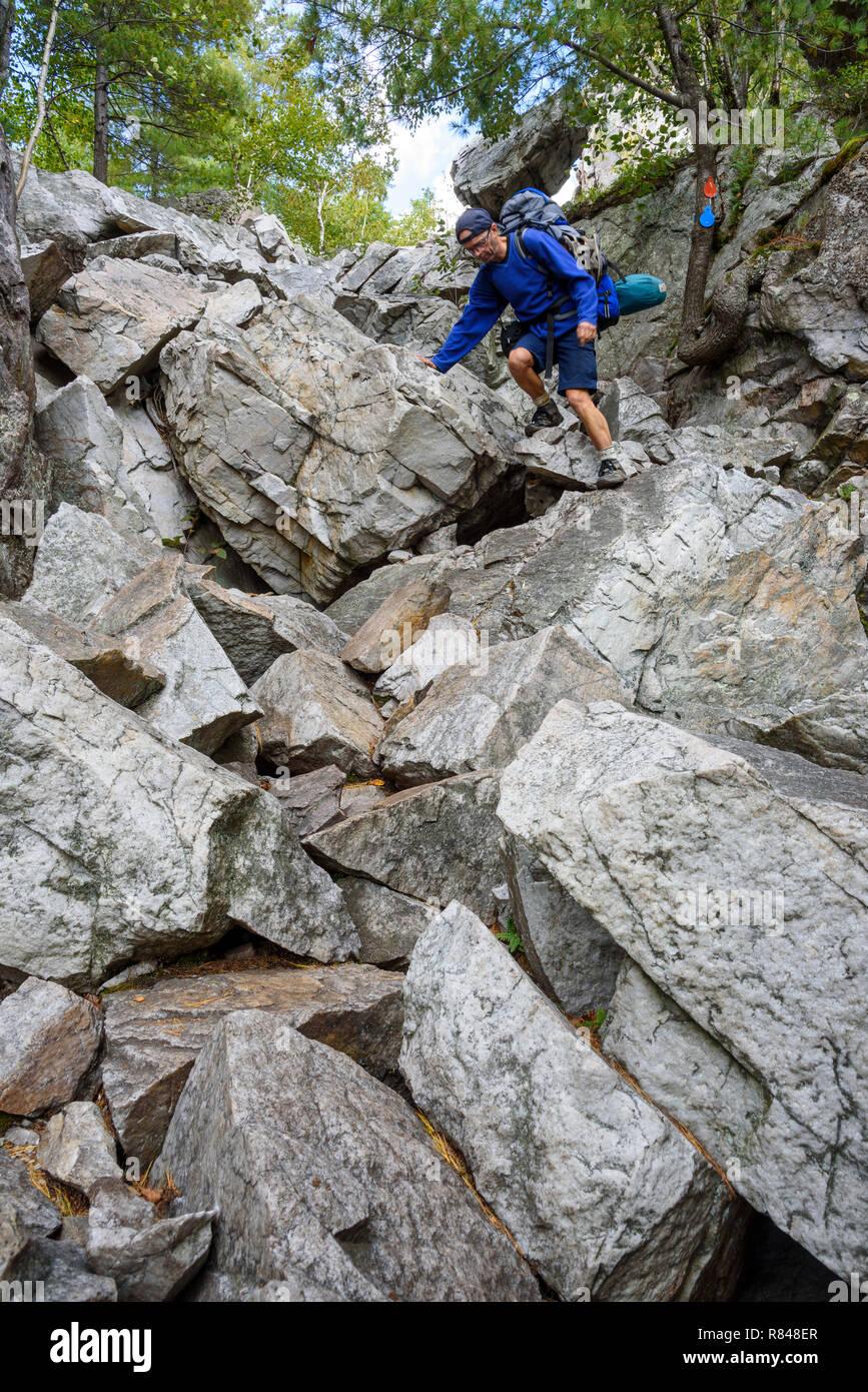 Hiker climbing The Crack, La Cloche Silhouette Trail, Killarney Provincial Park, Ontario, Canada - Stock Image
