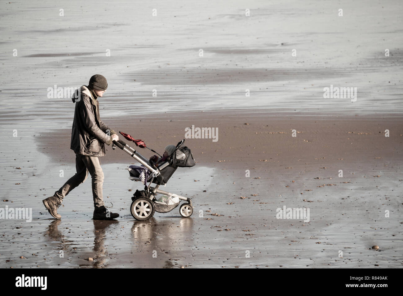 Man walking on beach pushing pushchair/pram.UK - Stock Image