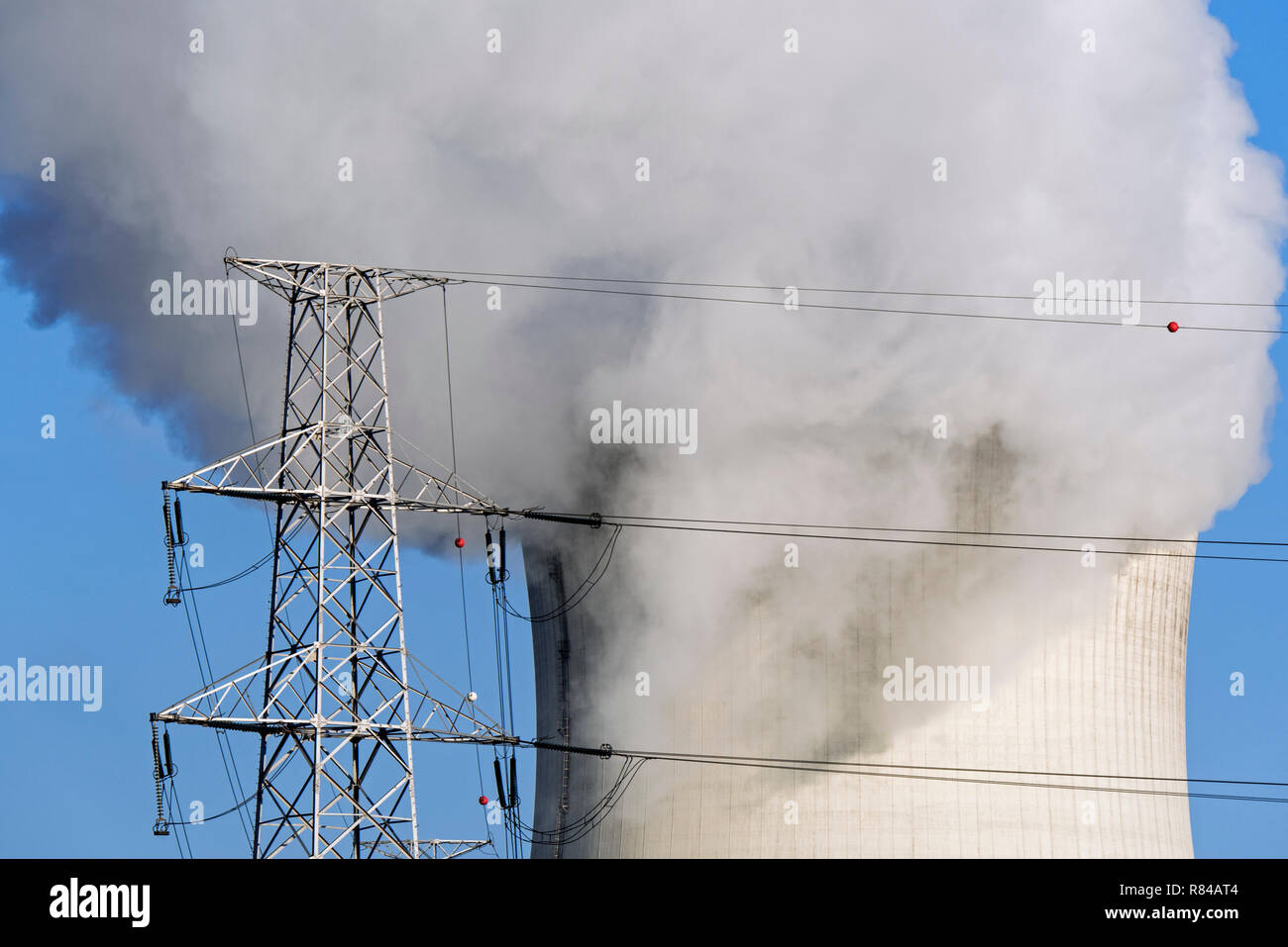 High-voltage electricity pylon / transmission tower and steam / vapour coming from cooling tower of nuclear power station / nuclear power plant - Stock Image
