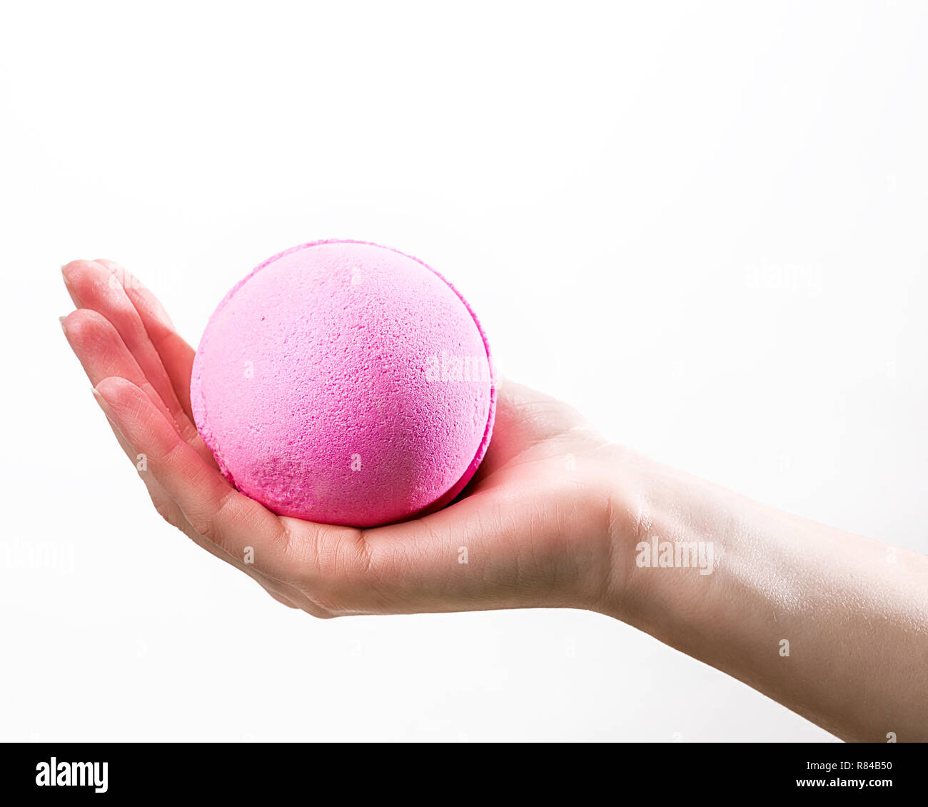 Female hand holding large pink bath bomb on the white background - Stock Image