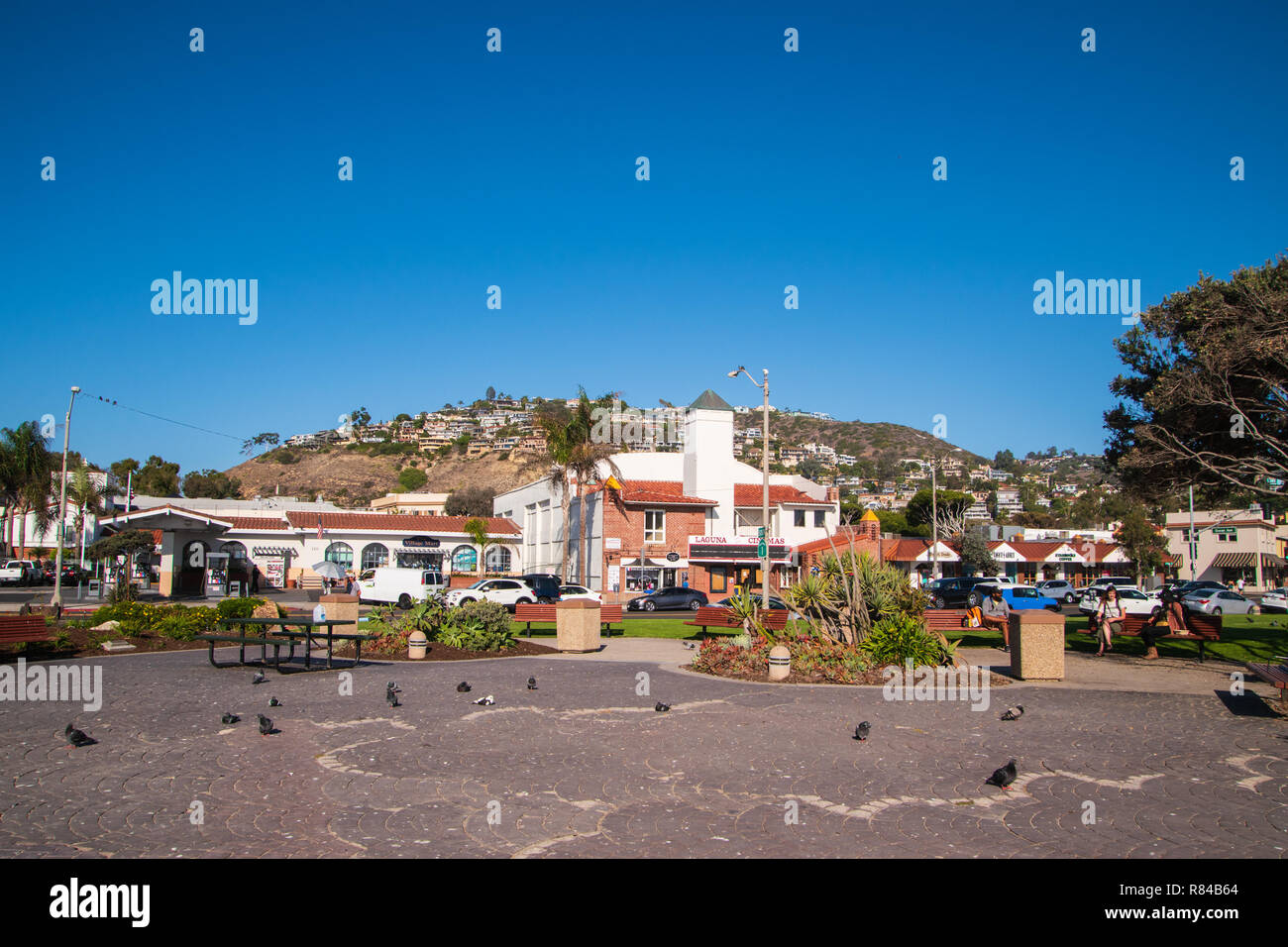 Laguna Beach, California - October 9, 2018: Housing development on the side of a mountain overlooking a small park with people relaxing on benches as  Stock Photo