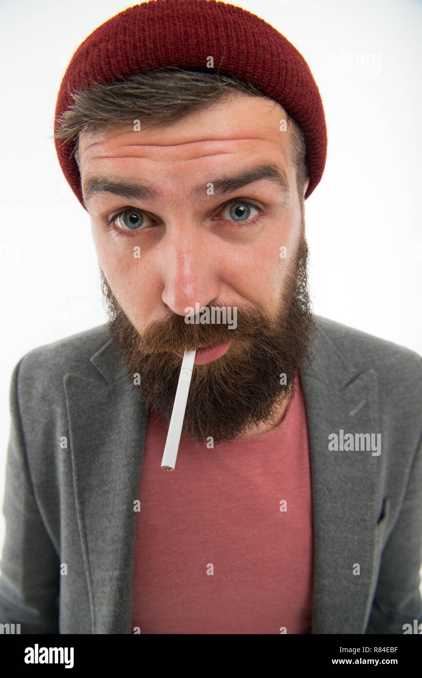Man brutal bearded hipster smoking cigarette. Brutal habits and lifestyle. Hipster brutal bearded tobacco smoker. Brutality and masculinity. Brutal unshaven guy smoking white background close up. - Stock Image