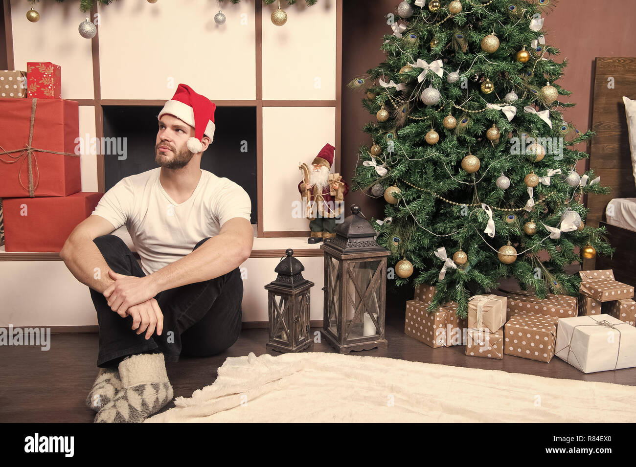 9c66ad88de840 Man in santa hat sit at fireplace. Macho at Christmas tree with present  boxes. xmas and new year room interior. Boxing day concept.
