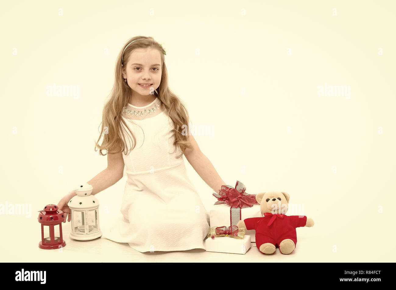 Child or happy kid with present pack isolated on white background. Small girl with gift box with red bow in dress. Christmas and birthday. Holiday celebration and mothers day. Childhood and happiness. Stock Photo