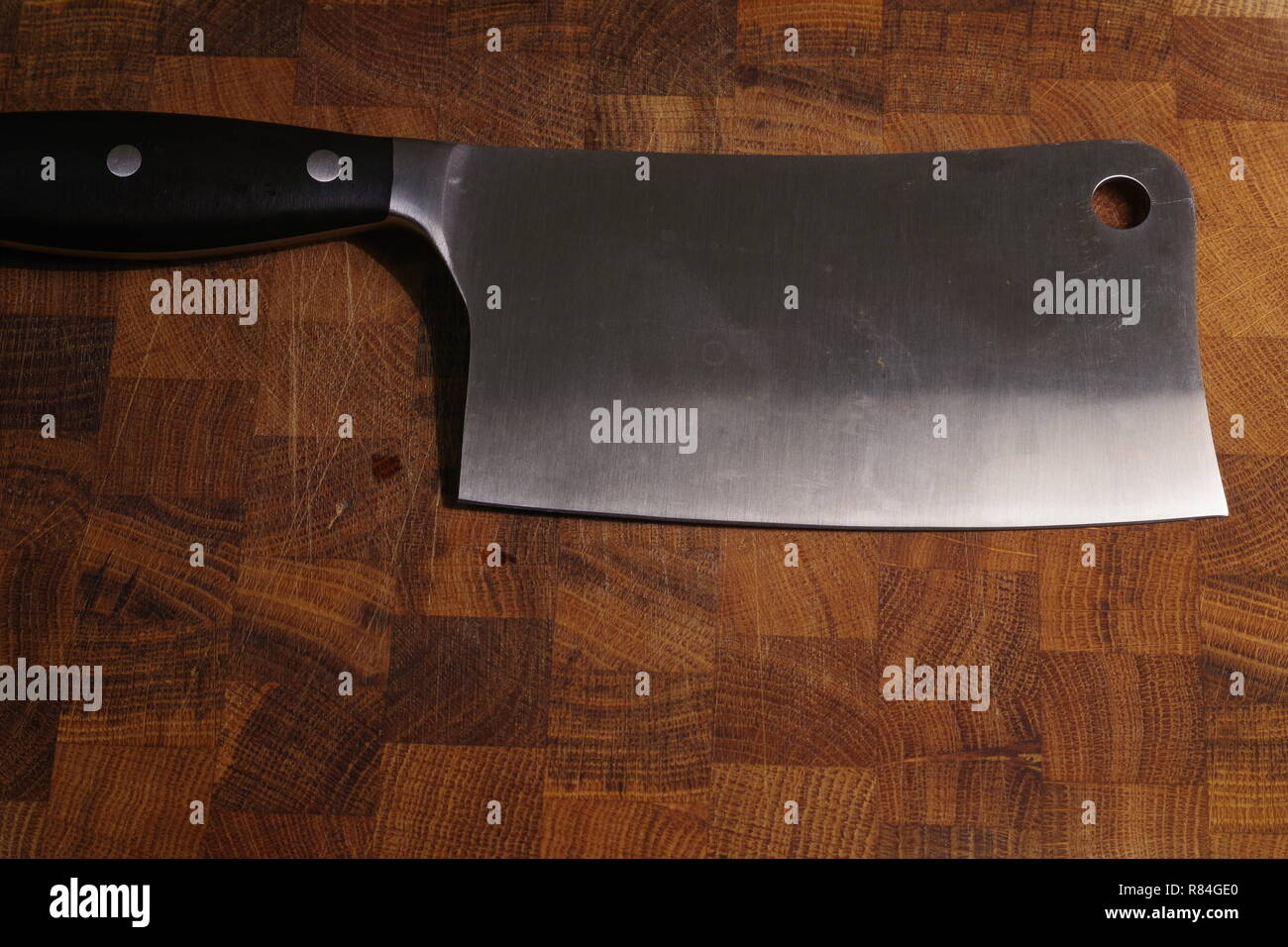 Close up of a Meat Cleaver Knife on an Oak Cutting Board. Kitchen, Cooking Still life. Aberdeen, Scotland, UK. - Stock Image