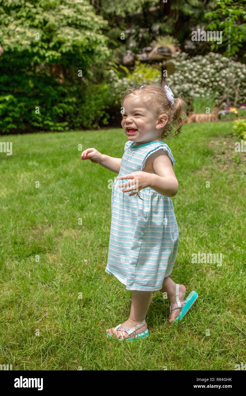 Issaquah, Washington, USA.  18 month old girl having fun exploring a backyard.  (MR) - Stock Image