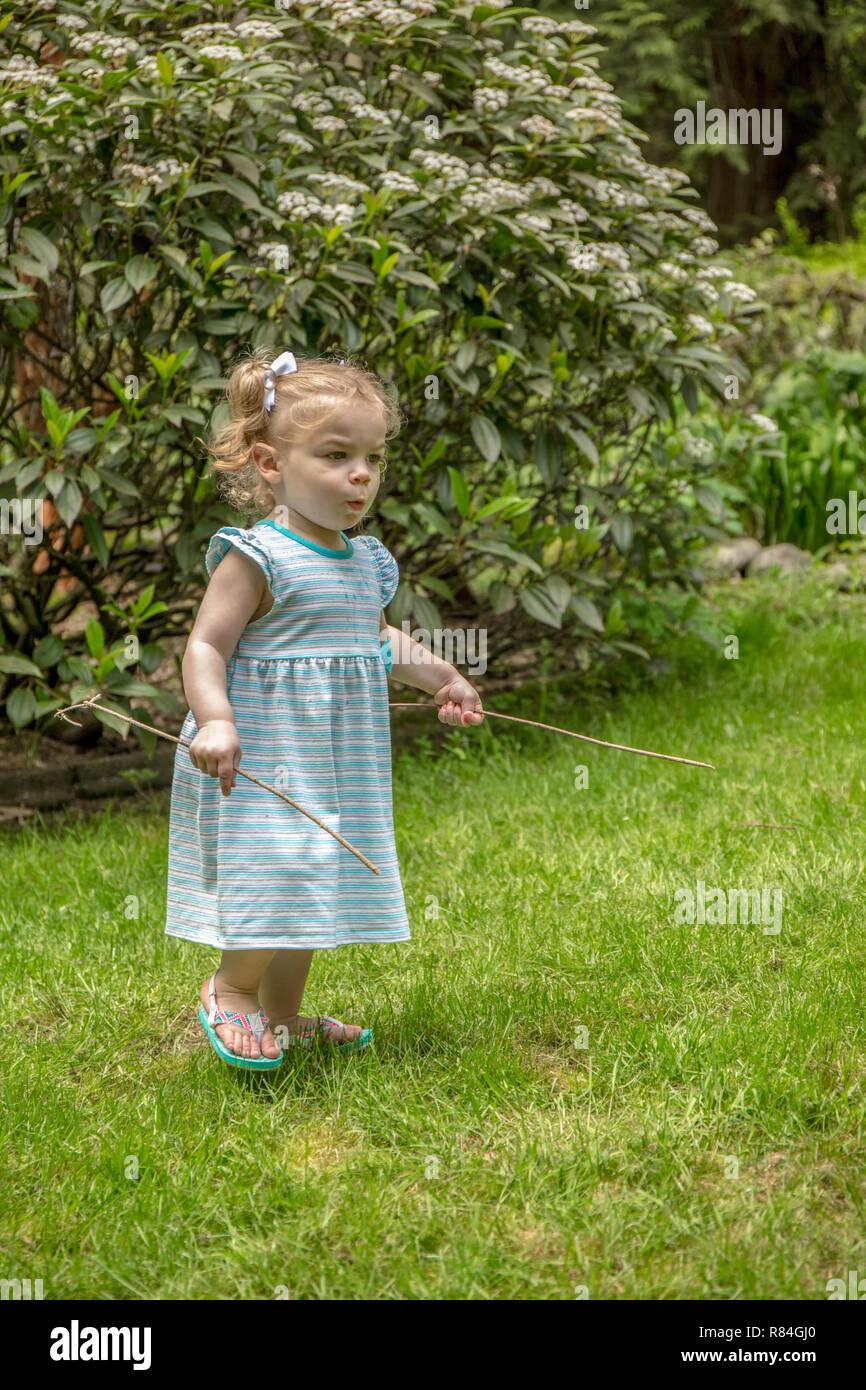 Issaquah, Washington, USA.  18 month old girl having fun with sticks while exploring a backyard.  (MR) - Stock Image
