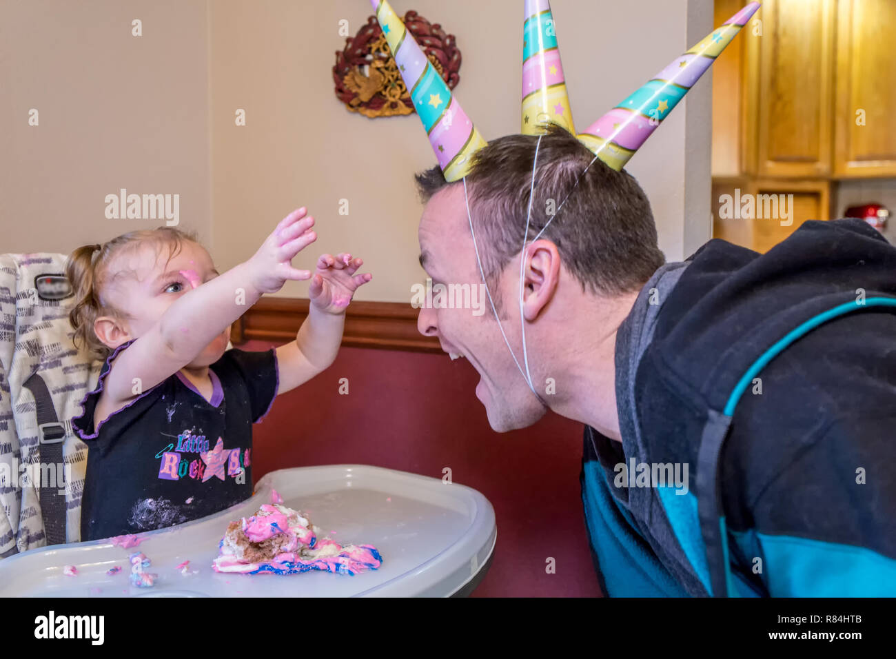 One year old reaches for her Dad's three unicorn hats.  (MR) - Stock Image