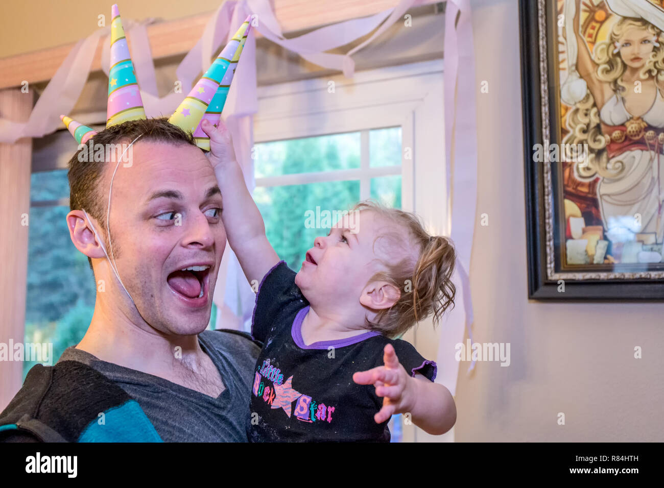 One year old girl trying to get one of her Dad's three unicorn hats at her birthday party.  (MR) - Stock Image