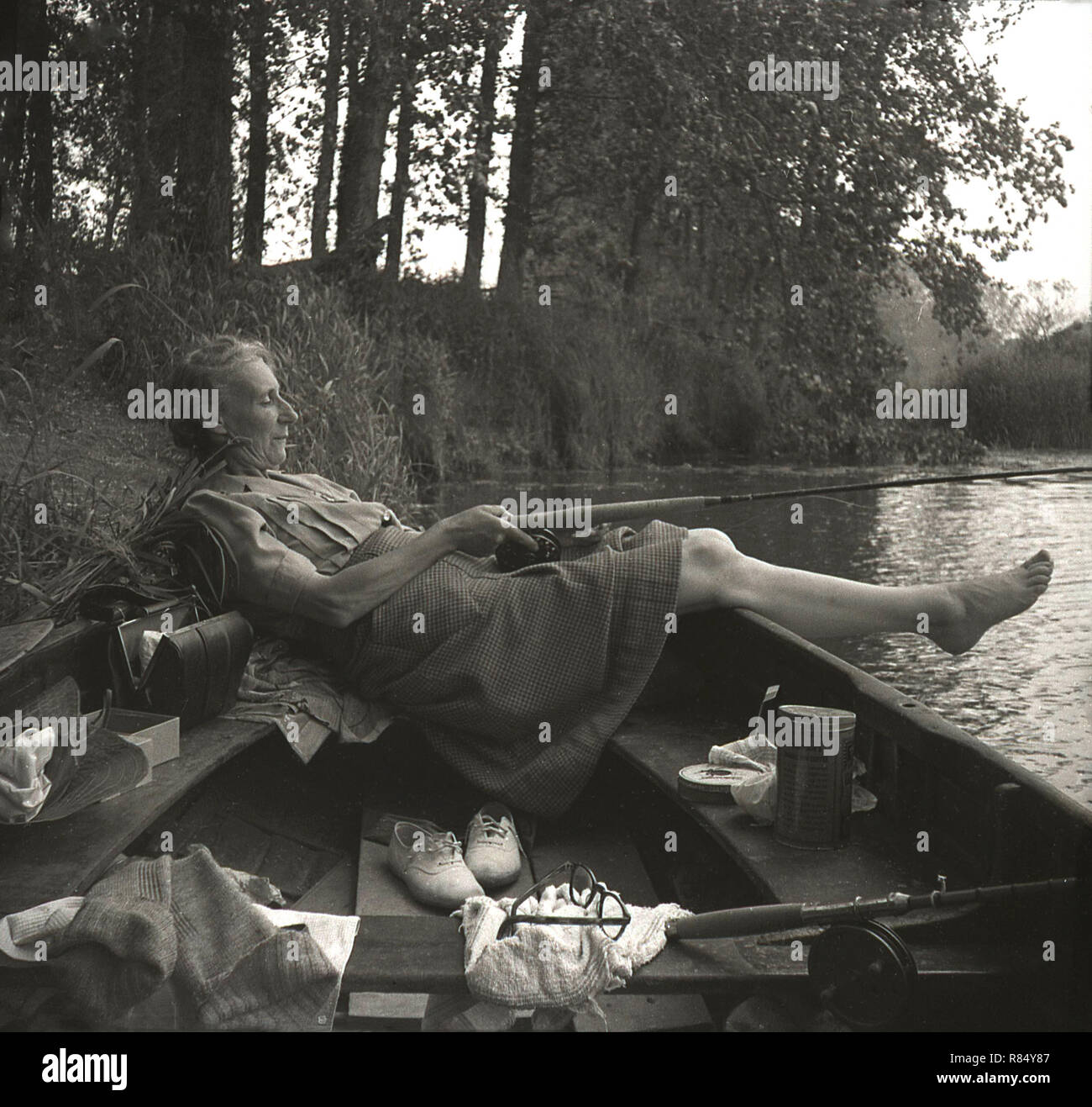 1950s, Elderly lady in barefeet lying back in a rowing boat at a river's edge holding a fishing rod, England, UK. - Stock Image