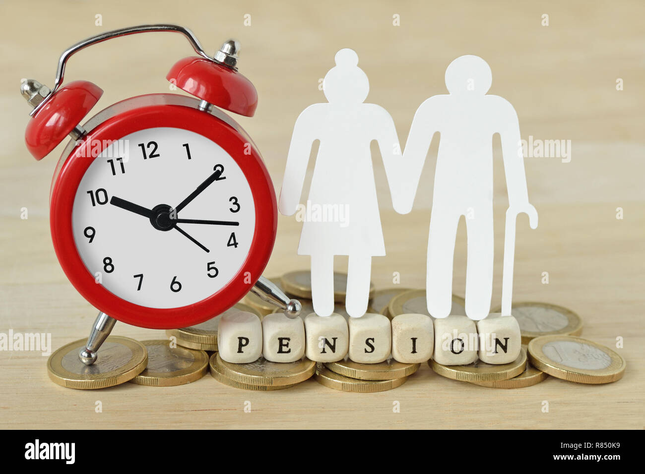 The word Pension written with wooden blocks, paper elderly couple and alarm clock on coins - Pension time concept - Stock Image