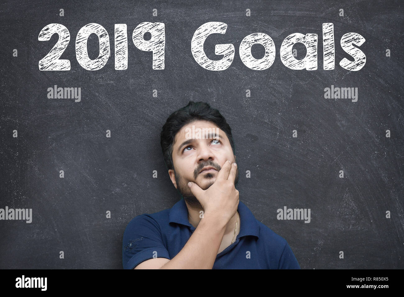 Thinking Position of A Young Asian Man while standing against blackboard with chalk drawing of new year 2019 goals - Stock Image