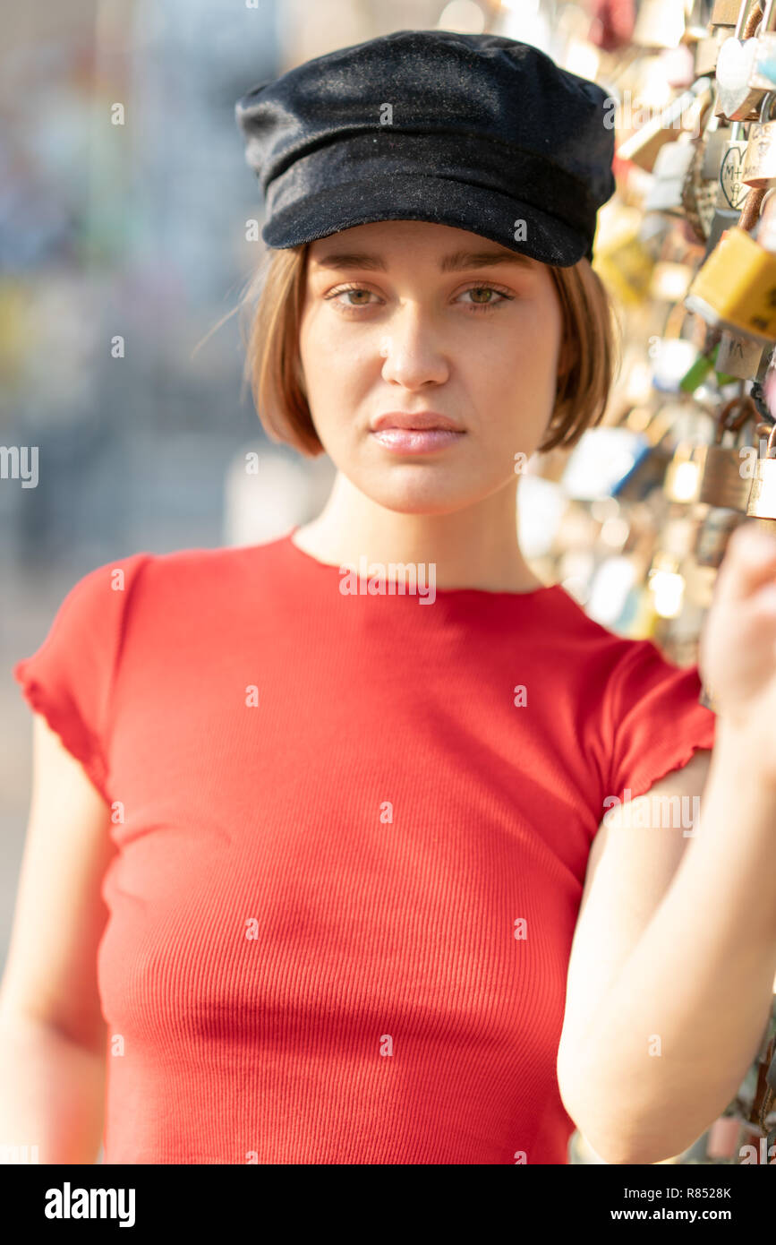 Portrait Of Young Woman With Short Hair Beanie And Red Top In The Street With A Fence Full Of Padlocks Stock Photo Alamy