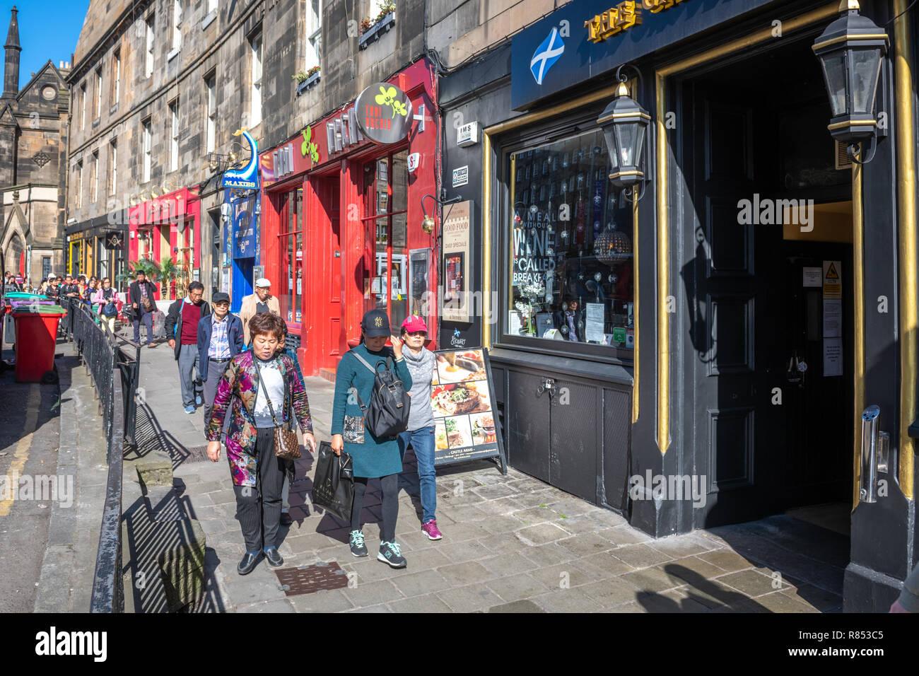 Asian tourists wander along an Edinburgh street after exploring and shopping throughout the city, Scotland, UK. - Stock Image
