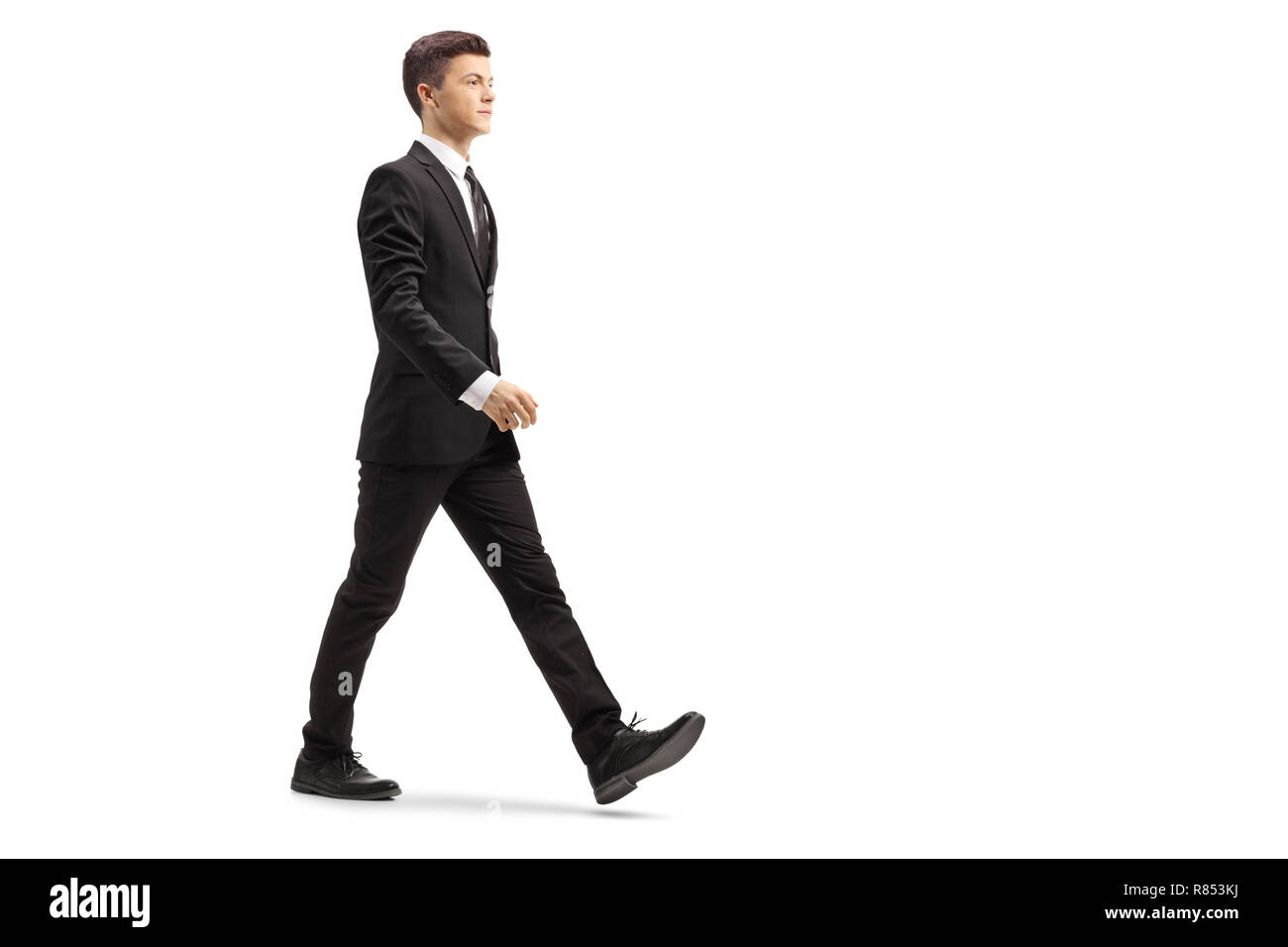 0297455957e3 Full length shot of a young handsome man in a black suit walking isolated  on white