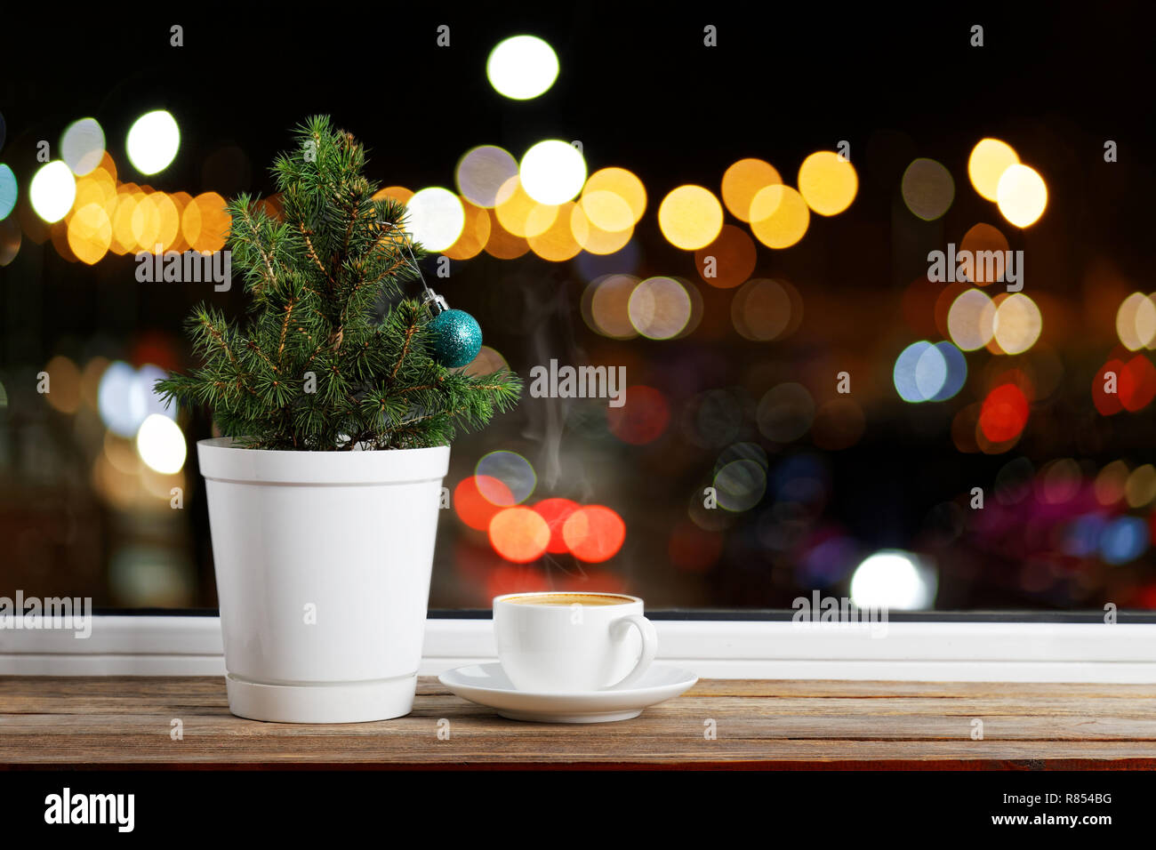 Small Christmas Tree In A Flowerpot Decorated With One Christmas Ball On A Wooden Window Sill Nearby Is A Cup Of Coffee Outside The Window Are Color Stock Photo Alamy
