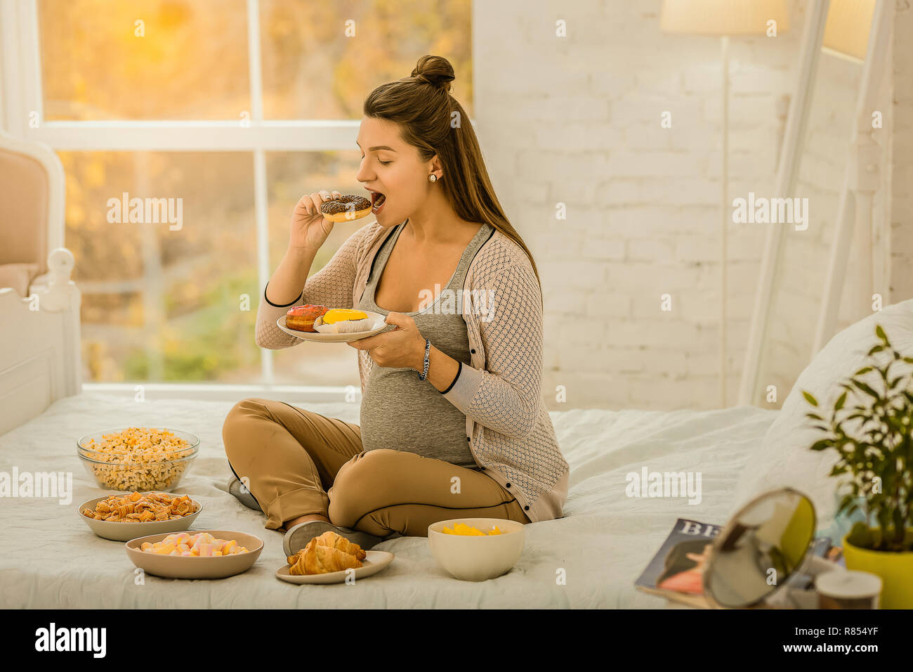 The pregnancy diet  The woman eating a lot of sweets while pregnancy
